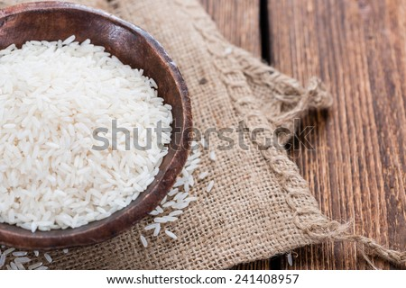 Portion of Rice on rustic wooden background (close-up shot) - stock photo