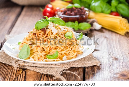 Portion of Spaghetti with Tomato Pesto, Basil and Parmesan Cheese - stock photo
