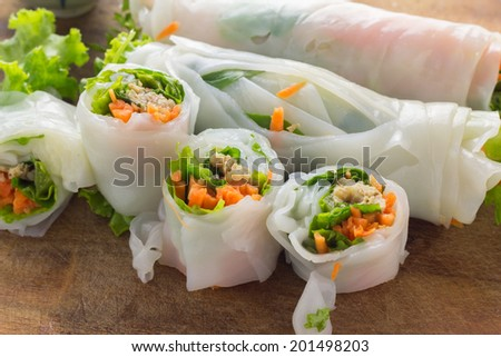 Portion of spring rolls on old wood with spicy sauce, vegetables and in noodle tube - stock photo