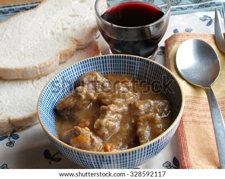 Portion of traditional beef stew with carrots in a bowl with wine and bread   - stock photo