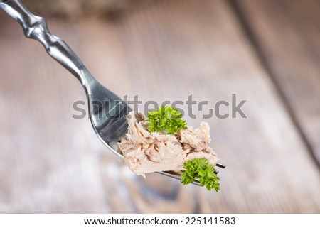 Portion of tuna (with parsley) on a fork as detailed close-up shot - stock photo