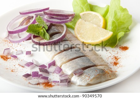 Portion of typical Dutch herring on the plate and on white Background - stock photo