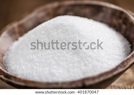 Portion of White Sugar (detailed close-up shot; selective focus) on wooden background - stock photo