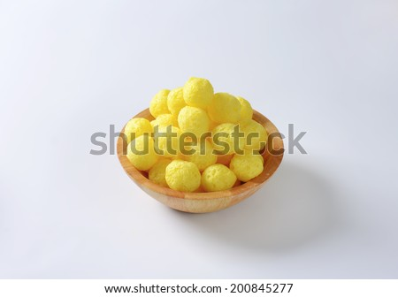 portion of yellow corn puffs in the wooden bowl - stock photo