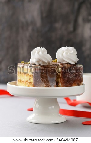 portioned dessert piece of cake with cream and chocolate on a plate - stock photo