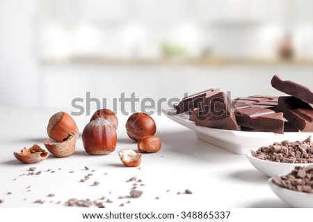Portions and chocolate chips with hazelnuts on a white porcelain container on a white table in kitchen. Horizontal composition. Front view - stock photo