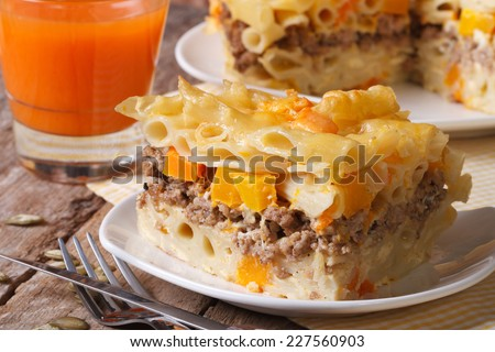 portions of pasta penne baked with meat, cheese and pumpkin close up. horizontal   - stock photo