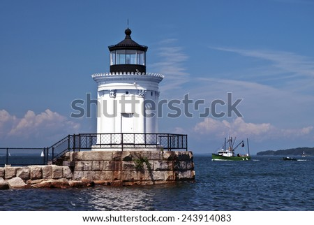Portland Breakwater lighthouse, also known as Bug light, guides a fishing trawler into the harbor. - stock photo