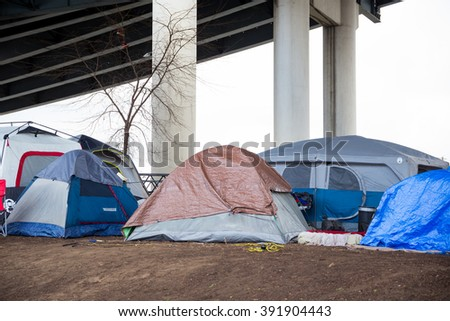 PORTLAND, OR - FEBRUARY 27, 2016: Homeless camps with tents and tarp shelter under a bridge in downtown Portland Oregon. - stock photo