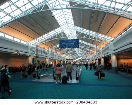PORTLAND, OR - MAY 27, 2014: People walk to terminals with bags at PDX, Portland International Airport which is a major transportation hub in the northwest coast of USA.   - stock photo