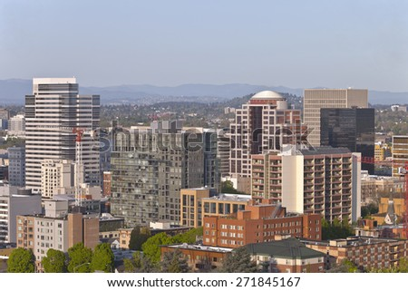 portland Oregon downtown buildings and construction cranes at sunset. - stock photo