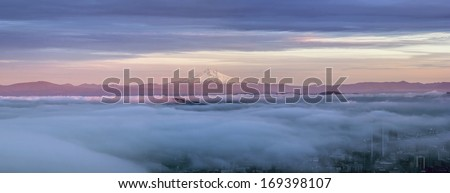 Portland Oregon Downtown Covered in Fog at Sunset with Mount Hood Panorama - stock photo