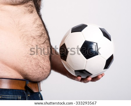 portly belly of a man with black and white football - stock photo
