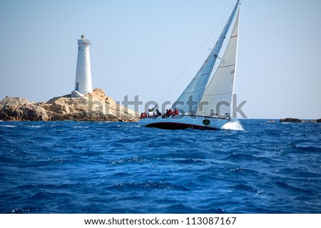 PORTO CERVO, ITALY - SEPTEMBER 12:  Sailing team in front of Monaci Lighthouse compete in the  Rolex Swan Cup boat race on September 12, 2012 in Porto Cervo, Italy. - stock photo