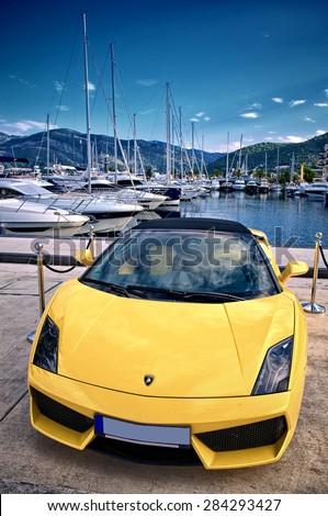 PORTO MONTENEGRO, TIVAT, MONTENEGRO - YULY 18: yellow Lamborghini Gallardo parking in reserved area superyacht marina of Porto Montenegro. Shot in 2014 - stock photo