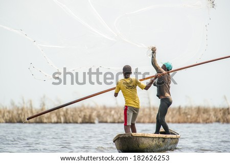 PORTO-NOVO, BENIN - MAR 9, 2012: Unidentified Beninese father throws the fish net into the water and his son helps him. People of Benin suffer of poverty due to the difficult economic situation. - stock photo