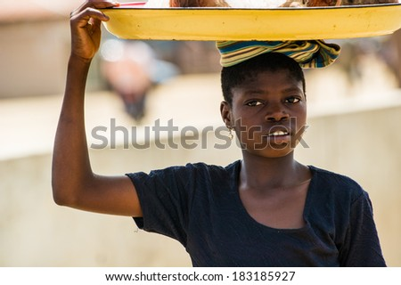 PORTO-NOVO, BENIN - MAR 9, 2012: Unidentified Beninese woman with a tray over the head. People of Benin suffer of poverty due to the difficult economic situation - stock photo