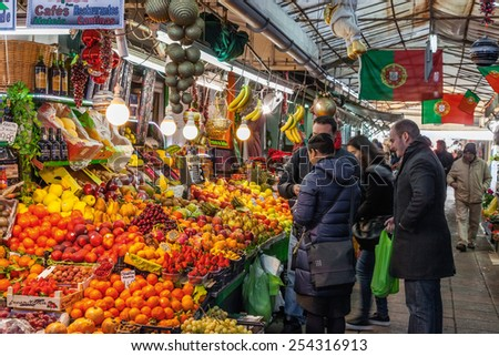 Porto, Portugal. December 29, 2014: Fruit seller and buyers in the interior of the historical Bolhao Market - stock photo