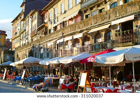 PORTO, PORTUGAL - JAN 12, 2015: Unidentified people at street restaurant on the embankment of Porto. Porto historical core was proclaimed a World Heritage Site by UNESCO in 1996 - stock photo
