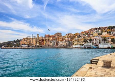 Porto Santo Stefano harbor seafront, bolllard and village skyline., italian travel destination. Monte Argentario, Tuscany, Italy. - stock photo