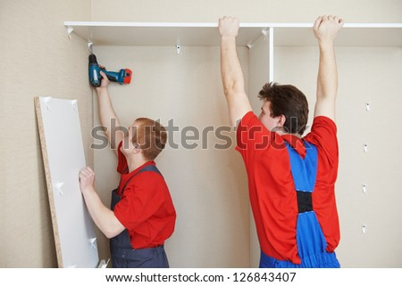 Portraait of Craftsman carpenter at kitchen cabinet installation service work - stock photo