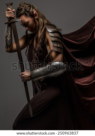 Portrai of mystic  elf woman with sword, armor and tattoo on her hand. A side view portraite. - stock photo