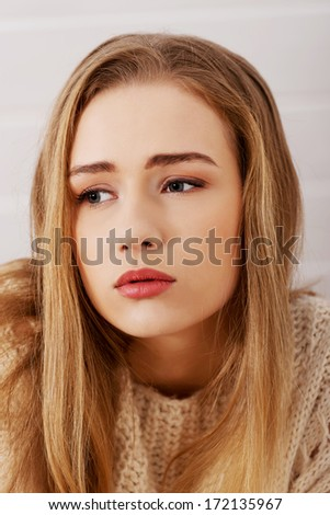 Portraif of beautiful sad, worried caucasian woman in bright sweater. - stock photo