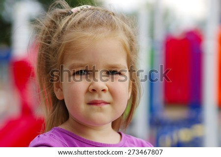 Portrait a little girl on playground. Happy smiling child playing on outdoor. - stock photo