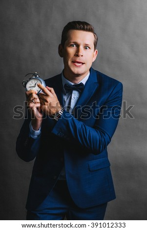 Portrait a man looking at the camera, point at alarm. Gray background.  Crazy  man with short medium  hair in business suit holding  alarm clock. remind you back to work - stock photo