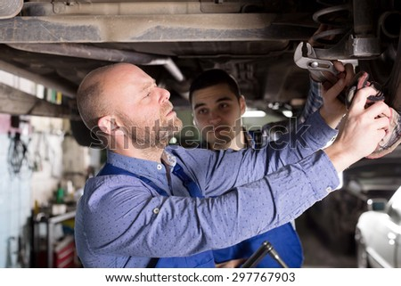 portrait adult  men in coveralls working at auto repair shop. - stock photo