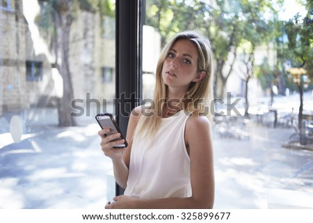 Portrait an attractive caucasian woman posing while holding her smart phone during work break,charming blonde female student chatting on her cell telephone during break between lectures in University  - stock photo