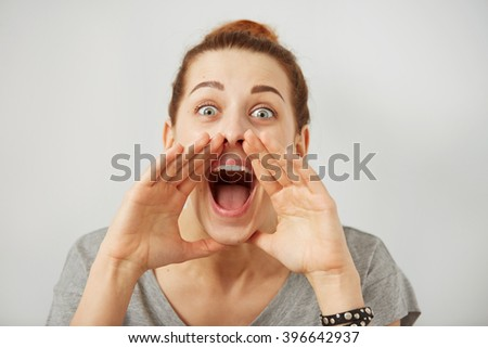 Portrait angry woman screaming, wide open mouth, hysterical isolated grey wall background. Negative human face expressions, emotion, bad feelings reaction. Conflict, confrontation concept. - stock photo