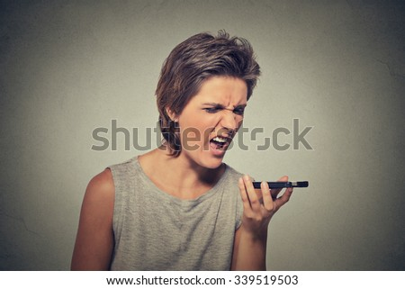 Portrait angry young woman screaming on mobile phone isolated on gray wall background. Negative emotions feelings  - stock photo