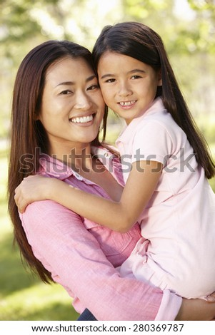 Portrait Asian mother and daughter outdoors - stock photo
