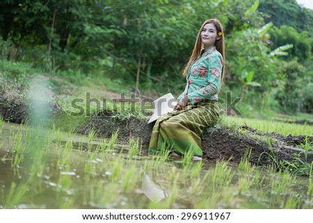 Portrait attractive asian girl sitting relaxed smiling in rural farming area in outback at thailand - stock photo