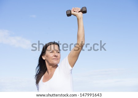 Portrait attractive confident middle aged woman exercising with weights, keeping healthy and fit, focused view, determined, positive, successful, with blue sky as background and copy space. - stock photo