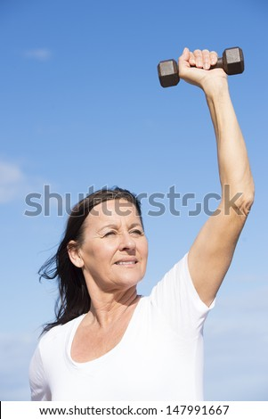 Portrait attractive confident middle aged woman exercising with weights, keeping relaxed healthy and fit, focused view, determined, positive, successful, with blue sky as background and copy space. - stock photo