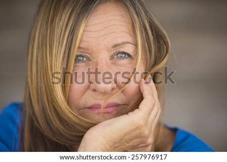 Portrait attractive mature lady in relaxed confident pose, happy serious look, blurred background, copy space. - stock photo