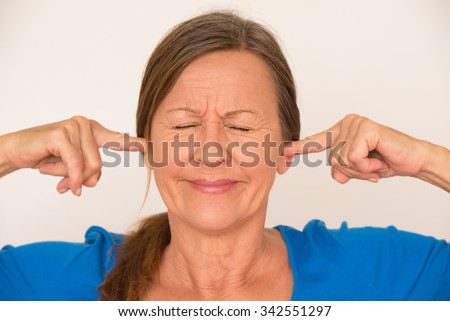Portrait attractive mature woman blocking noise from ears with finger, stressed facial expression, closed eyes, isolated, bright background. - stock photo