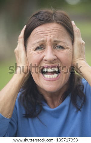 Portrait attractive mature woman covering frustrated, angry or in anxiety her ears with hands, upset stressed, isolated with blurred outdoor background. - stock photo