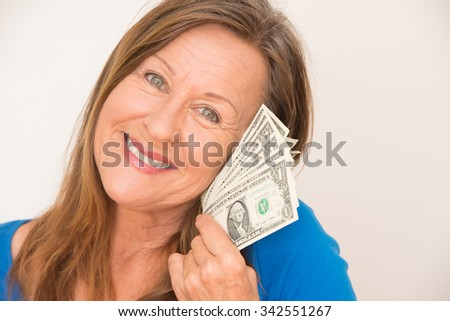 Portrait attractive mature woman holding joyful relaxed with us dollar notes, isolated, bright background. - stock photo