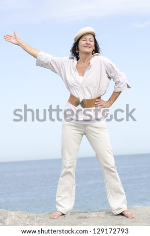 Portrait attractive mature woman, peaceful and relaxed with closed eyes, happy smiling, enjoying active retirement outdoor, isolated with ocean and white cloudy sky as background and copy space. - stock photo