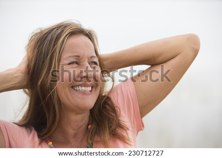 Portrait attractive mature woman posing happy joyful smiling with hands behind neck, enjoying active retirement, white background and copy space. - stock photo