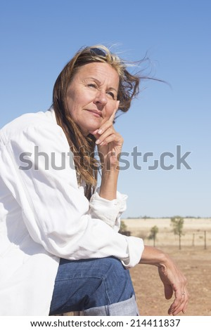 Portrait attractive mature woman sitting thoughtful, with happy confident face relaxed on hand, with rural country and blue sky as background. - stock photo