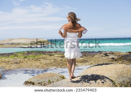 Portrait attractive mature woman standing relaxed in white summer dress on rocks at beach, turquoise colored ocean at Bay of Fire, Tasmania, with blue sky and horizon as background and copy space. - stock photo