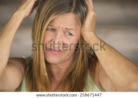 Portrait attractive mature woman tearing her long brunette hair with hands, unhappy, stressed, blurred background. - stock photo