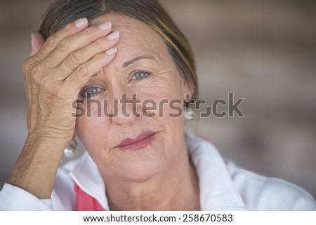 Portrait attractive mature woman with headache, painful migraine, stressful menopause, blurred background, copy space. - stock photo