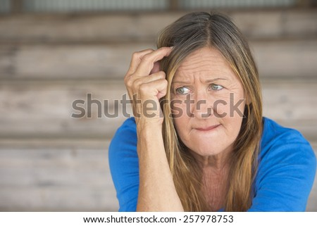 Portrait attractive mature woman with nervous thoughtful angry expression, lonely worried, blurred background. - stock photo