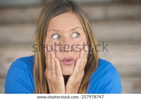 Portrait attractive mature woman with shocked, surprised, anxious, fearful facial expression, blurred background. - stock photo