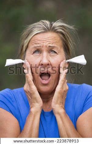 Portrait attractive mature woman with stressed suffering facial expression, with tissues in ears for noise protection, outdoor blurred background. - stock photo